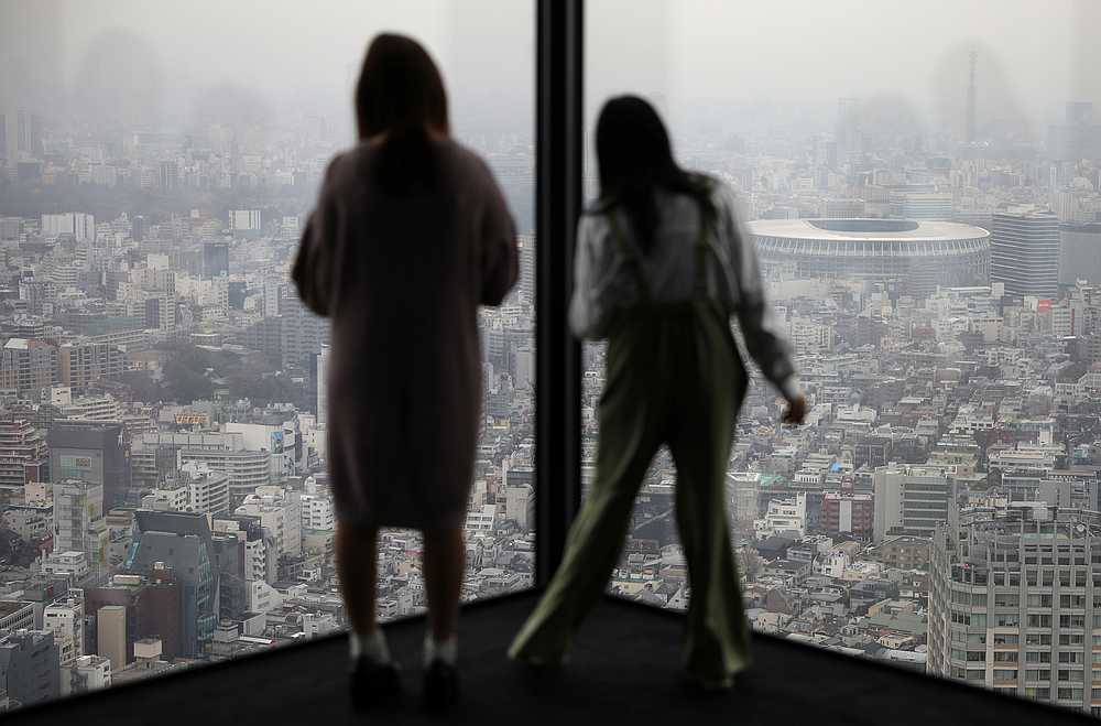 The new Olympic National Stadium is seen as women look at the Tokyo skyline from the Shibuya Sky Gallery in Tokyo, Japan March 4, 2020. — Reuters pic