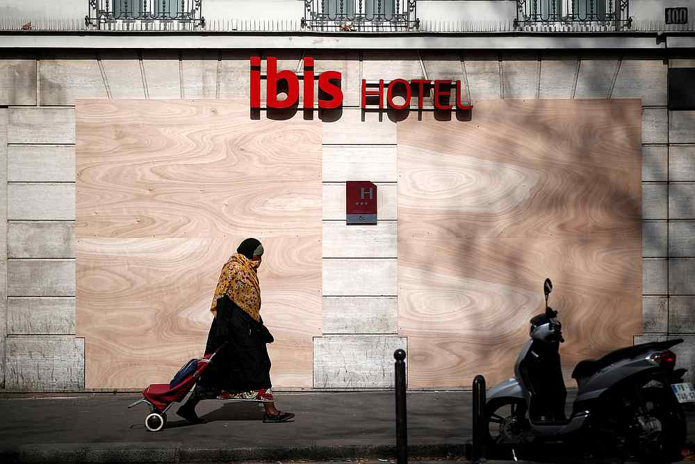 A woman passes by a closed main entrance of an Ibis hotel as a lockdown is imposed to slow down the spread of Covid-19 in France March 28, 2020. — Reuters pic