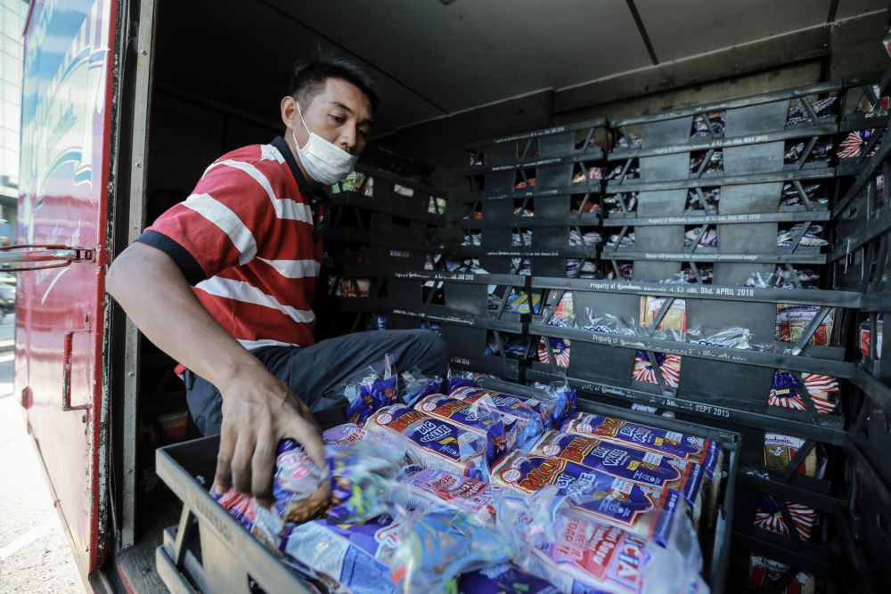A man unloads fresh loaves of bread at a convenience store in Petaling Jaya March 25, 2020. — Picture by Ahmad Zamzahuri