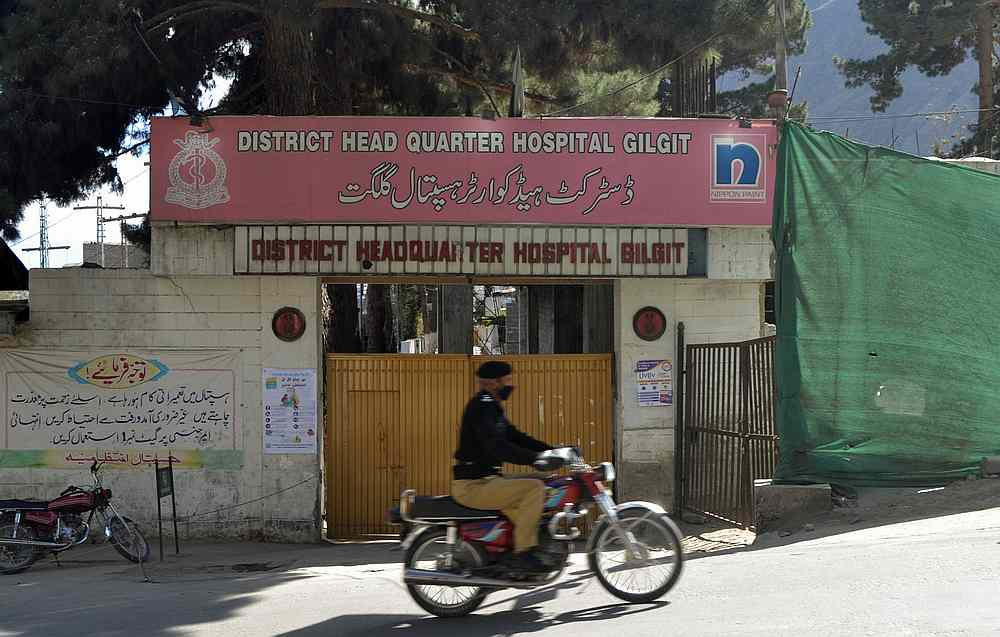 A police officer rides past a closed entrance of the district hospital, where a doctor who screened suspected Covid-19 patients tested positive and died, in Gilgit, Pakistan March 22, 2020. — Reuters pic