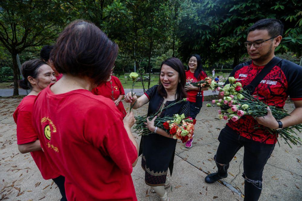Hannah Yeoh distributes carnations to park-goers at Taman Rimba Kiara, Petaling Jaya March 8, 2020. — Picture by Firdaus Latif