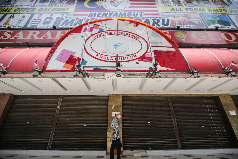 A man walks past shuttered shops along Jalan Tuanku Abdul Rahman as the movement control order kicks in on March 18, 2020. — Picture by Hari Anggara