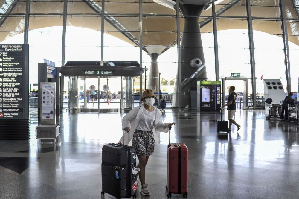 Travellers are pictured at the Kuala Lumpur International Airport in Sepang March 17, 2020. The AQMS uses 3D sensors that monitor real-time conditions from simple change in temperature and lighting conditions to complex algorithm that automatically detects long queues and wait times. — Picture by Shafwan Zaidon