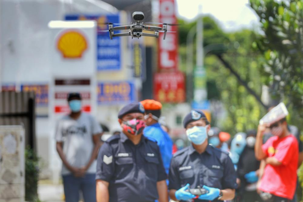 A drone is used by Malaysian police to monitor social distancing at the Chow Kit market in Kuala Lumpur March 27, 2020. ― Picture by Ahmad Zamzahuri