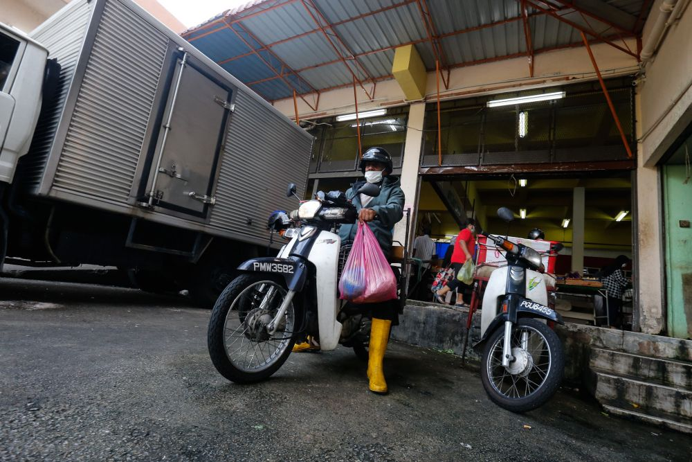 Zaihim Enterprise staff head out to make a delivery from the Taman Tun Sardon Wet Market in Penang March 26, 2020. — Sayuti Zainudin