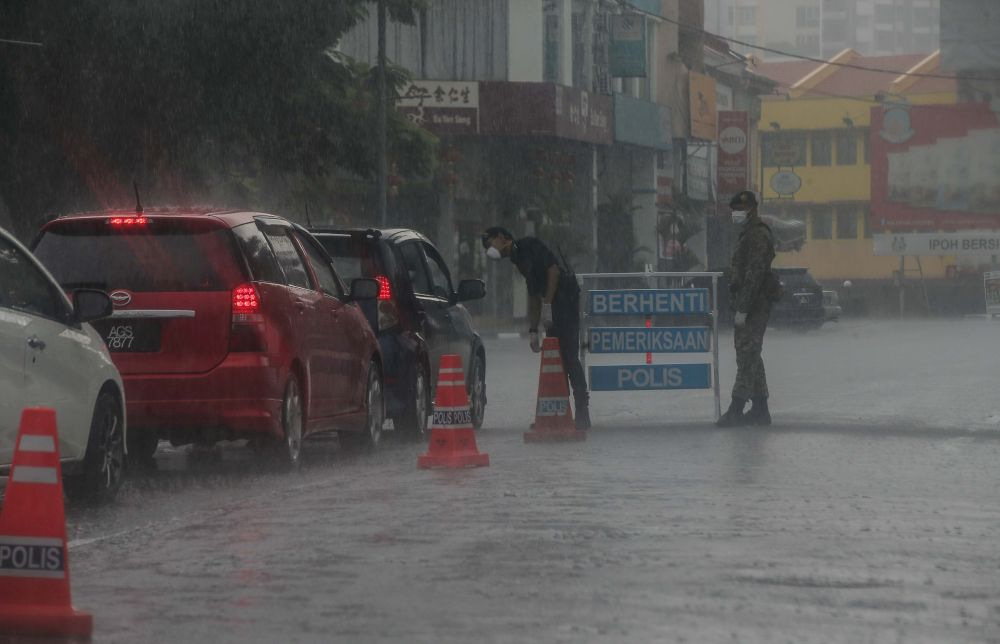 Malaysian Armed Forces and police personnel brave the heavy downpour to man a roadblock on Jalan Sultan Iskandar, Ipoh March 24, 2020. — Picture by Farhan Najib