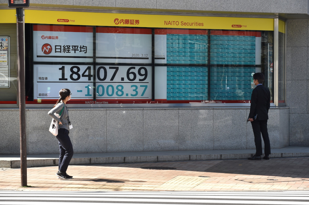 Pedestrians look at a quotation board displaying the share price numbers on the Tokyo Stock Exchange in Tokyo March 12, 2020. — AFP pic