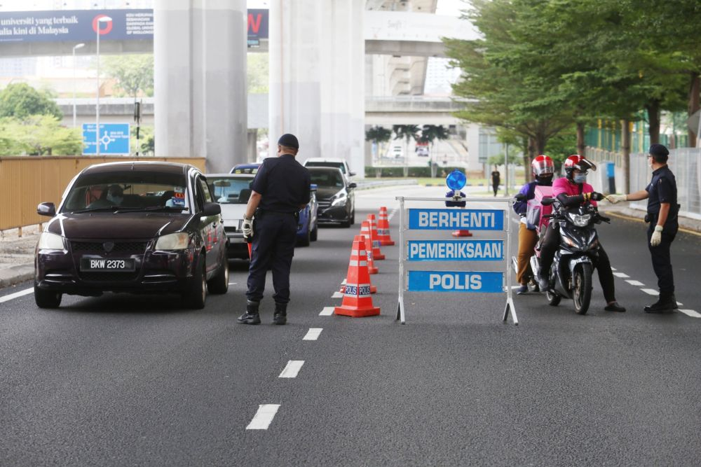 Police personnel inspect vehicles at a roadblock in Subang Jaya on Day Two of the movement control order March 19, 2020. — Picture by Choo Choy May