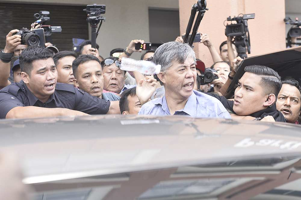PKR's Tian Chua heckled and jostled by PKR supporters in front of party headquarters in Petaling Jaya March 1, 2020. — Picture by Miera Zulyana