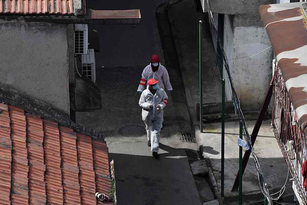 Volunteers in protective suits walk in between houses at a residential area in Wuhan, the epicentre of the novel coronavirus outbreak, Hubei province, China March 4, 2020. — Reuters pic