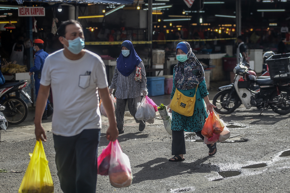 People shop for their essential goods at the Chow Kit market during the movement control order (MCO) in Kuala Lumpur April 5, 2020. — Picture by Firdaus Latif