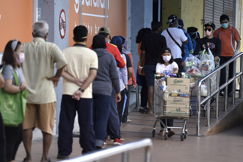 People keeping their distance from each other outside Giant Hypermarket during the movement control order (MCO) in Shah Alam April 5, 2020. — Picture by Miera Zulyana