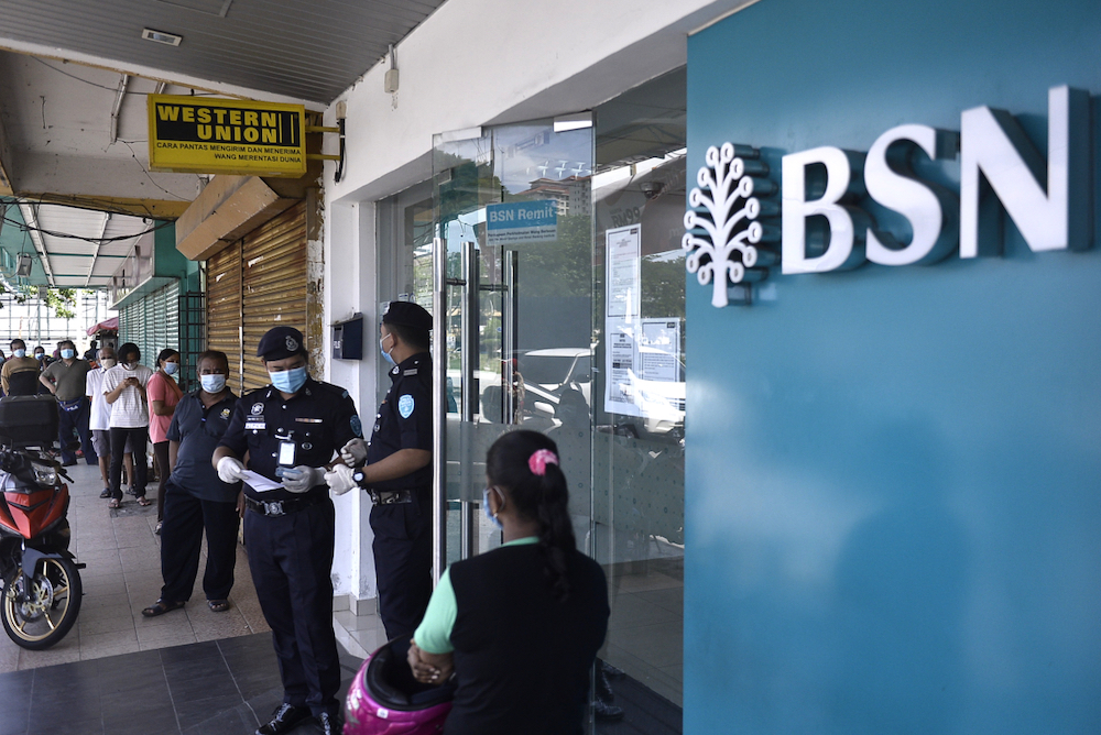 People queue in front of a Bank Simpanan Nasional branch in Kuala Lumpur April 6, 2020. Finance Minister Tengku Datuk Seri Zafrul Tengku Abdul Aziz says some 400,000 recipients of the Bantuan Prihatin Nasional (BPN) will receive cash payment via BSN branches. — Picture by Miera Zulyana