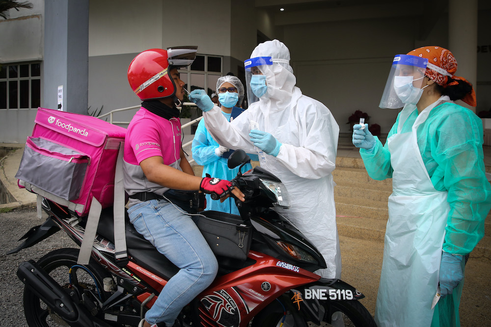 Health workers take coronavirus test samples of a food delivery rider at a drive-thru Covid-19 testing centre in Shah Alam April 18, 2020. — Picture by Yusof Mat Isa
