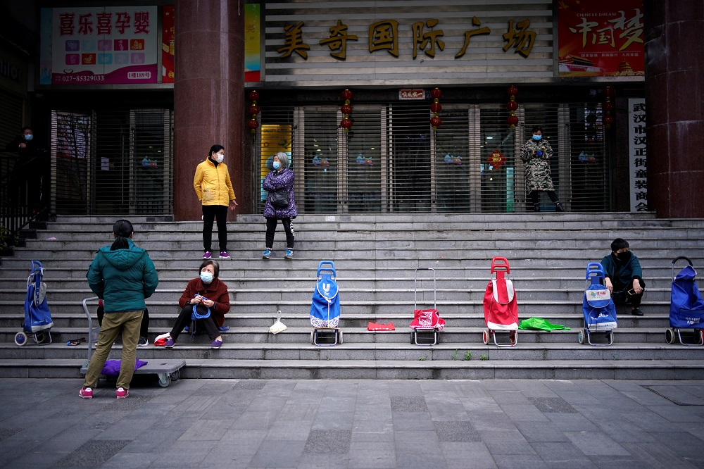 People wearing face masks wait for a supermarket to open in Wuhan, Hubei province April 5, 2020. — Reuters pic
