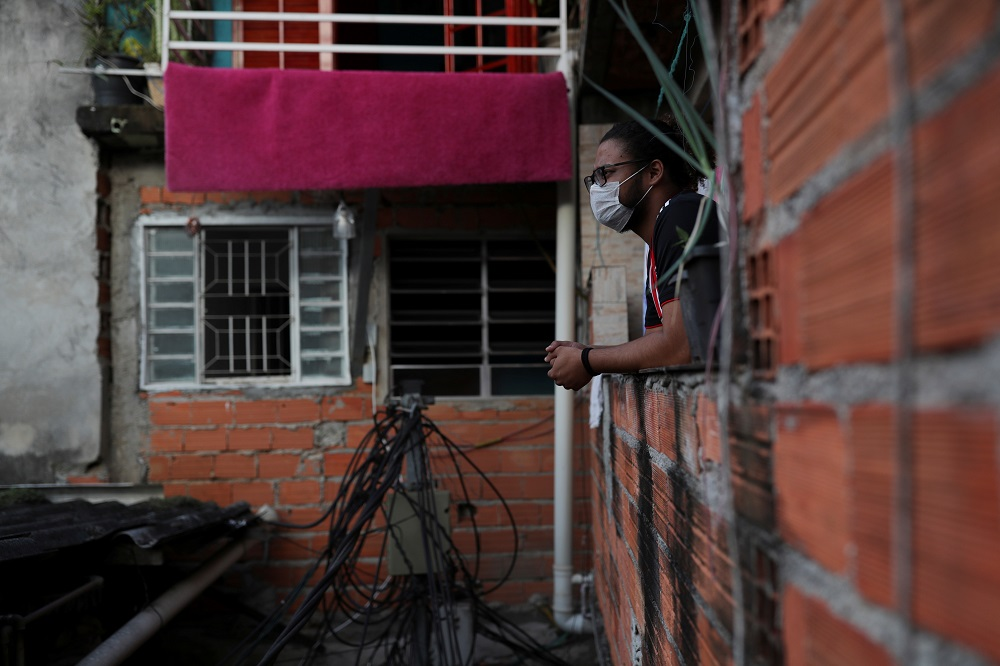 Marcus Vinicius Conceicao dos Santos, 22, looks out from his home as he self-isolates with another 19 people after showing symptoms of coronavirus disease, in the city's biggest slum Paraisopolis, in Sao Paulo March 30, 2020. — Reuters pic