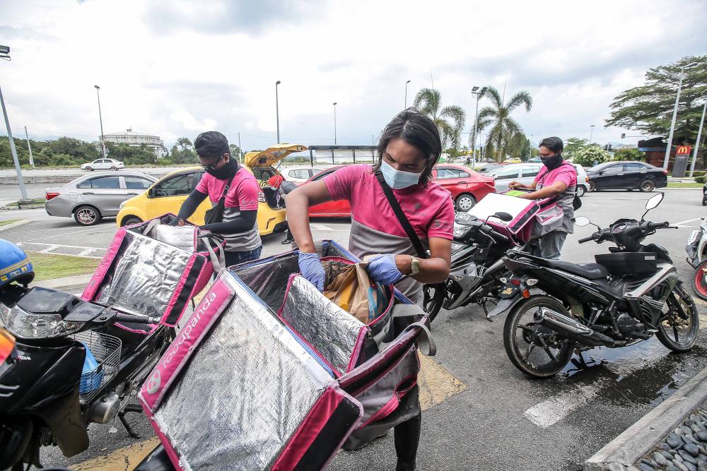 外卖小哥在店家拿到外卖要送去给顾客前,都要确保食物包装有没有破损和受到污染。-Farhan Najib摄-
