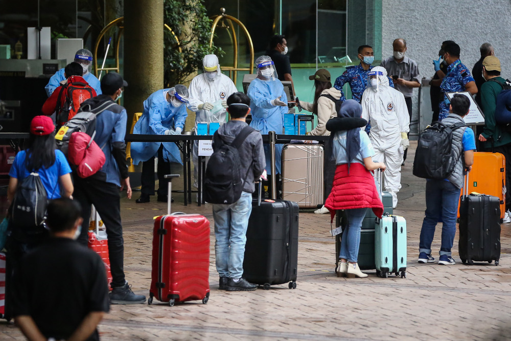 Malaysians returning from overseas queue to take a bus to a quarantine centre in Kuala Lumpur April 8, 2020. —Picture by Yusof Mat Isa