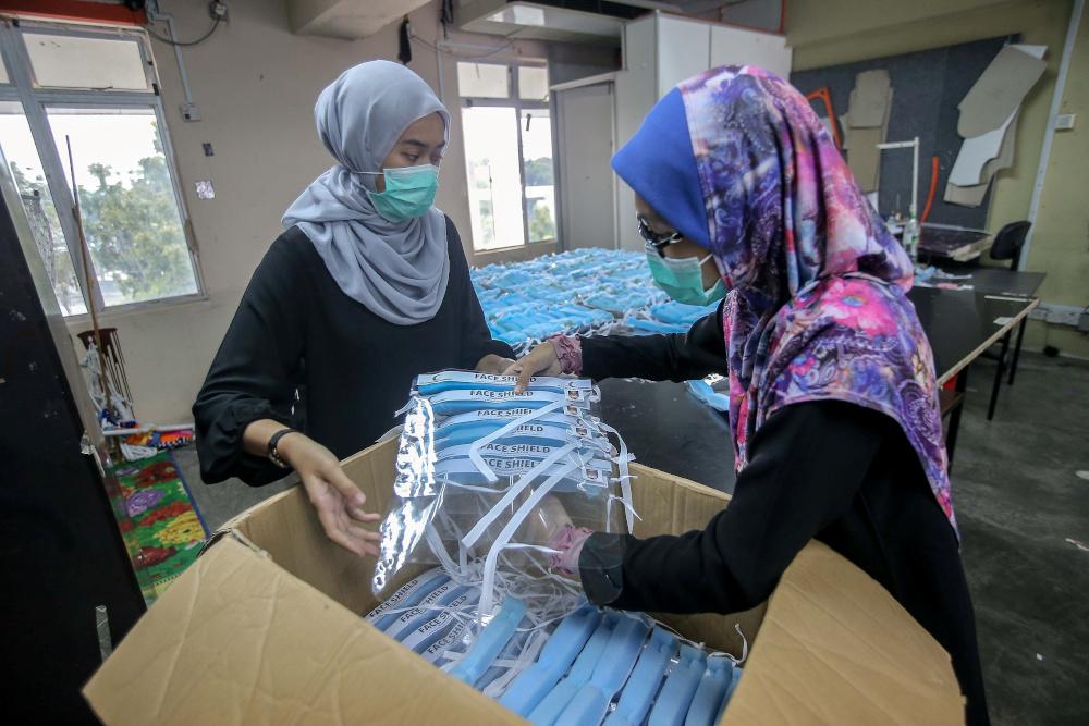 People work on a collaborative project between FSSR UiTM Perak, FSSR Shah Alam, UiTM Sg Buluh, Red Crescent Perak to produce personal protective equipment (PPE) at UiTM Seri Iskandar Art and Fashion workshop April 9, 2020. — Picture by Farhan Najib