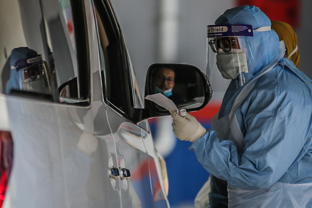 A medical worker takes a swab at a Covid-19 drive-through screening area at in Ampang April 9, 2020. — Picture by Hari Anggara