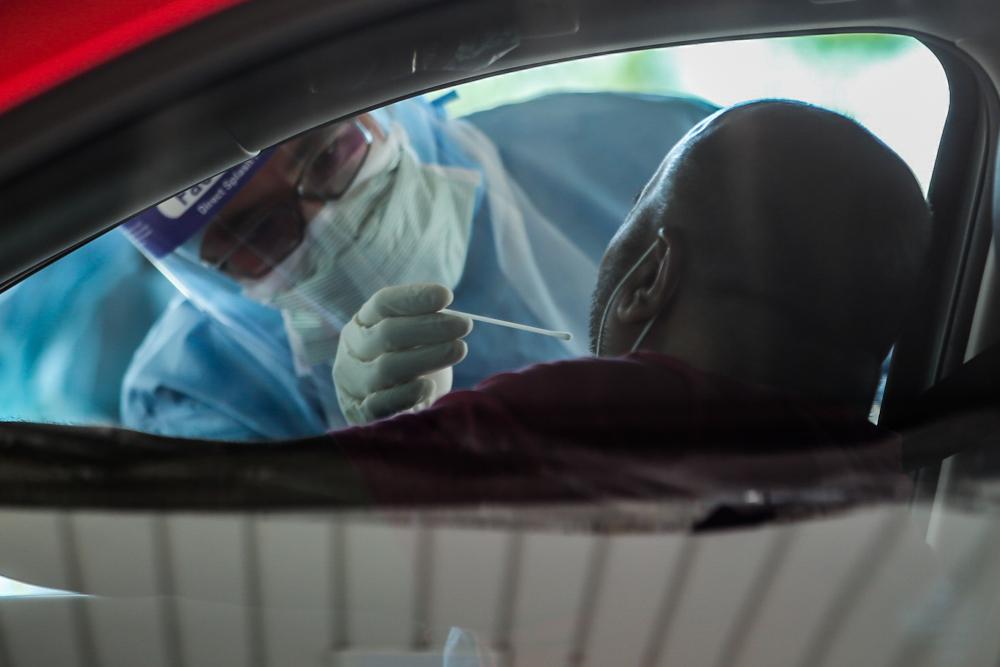 A medical worker takes a swab at a Covid-19 drive-through screening area at KPJ Ampang Puteri April 9, 2020. — Picture by Hari Anggara