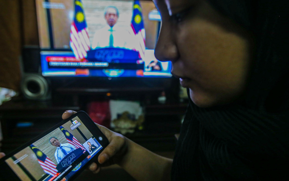 People watch the live telecast of the Prime Minister Tan Sri Muhyiddin Yassin announcing the extension of the movement control order due to the Covid-19 pandemic in Kuala Lumpur April 10, 2020. — Picture by Hari Anggara