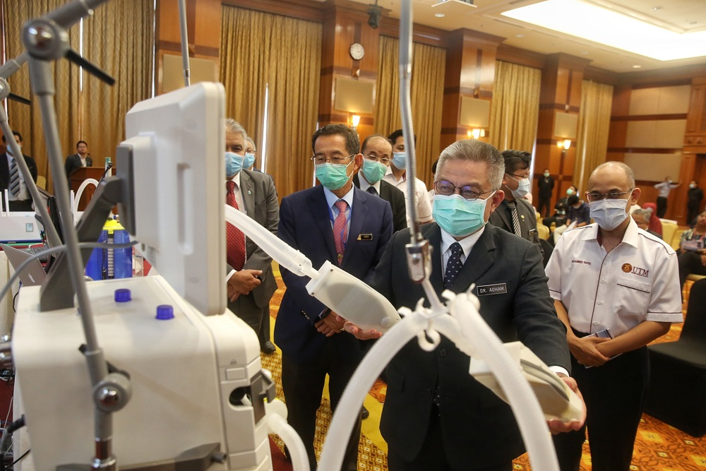 Health Minister Datuk Sri Dr Adham Baba (second right) inspects a prototype splitter kit during a media briefing at the Health Ministry in Putrajaya April 13, 2020.