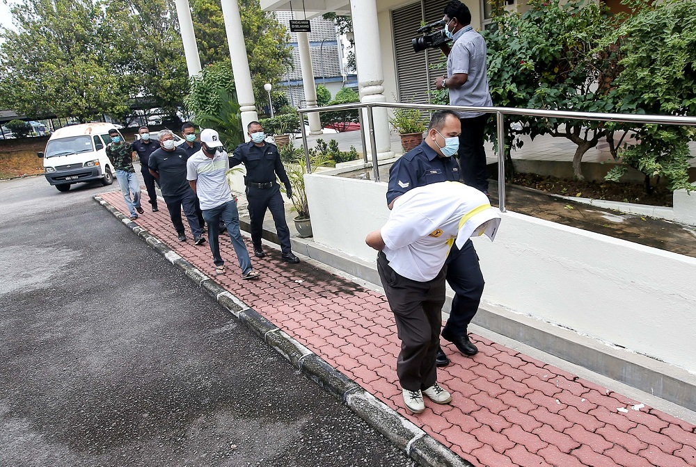 The three men who defied the movement control order by playing golf are led in handcuffs to the Magistrate Court in Batu Gajah April 17, 2020. — Picture by Farhan Najib