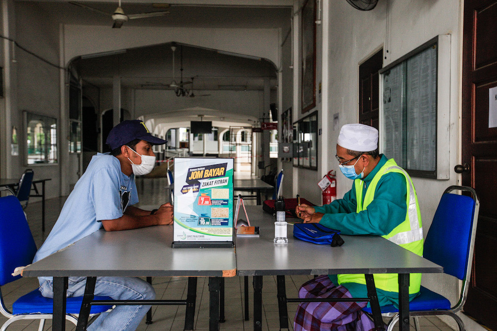 File picture shows a man paying his zakat fee to the Amil or the zakat collector at Masjid Jamek Seberang Jaya, April 30, 2020. — Picture by Sayuti Zainudin