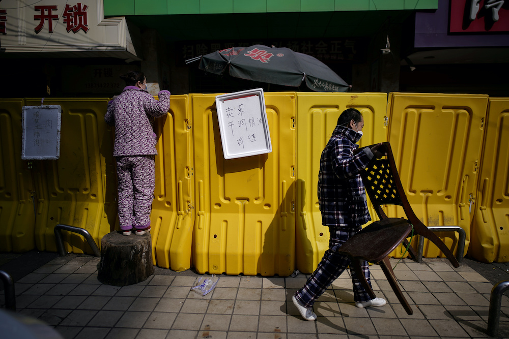 A resident pays for groceries by standing on a tree stump to peer over barriers set up to ring fence a wet market on a street in Wuhan, Hubei province, the epicentre of China's coronavirus disease (Covid-19) outbreak, April 1, 2020. — Reuters pic
