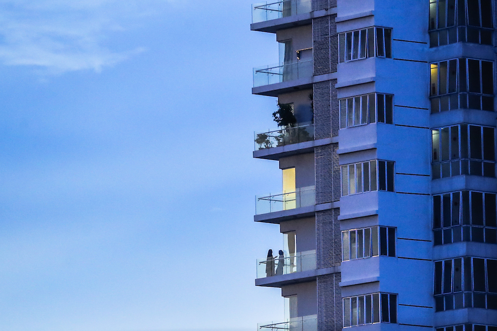 People are pictured seen at the balcony of an apartment in Kuala Lumpur April 4, 2020. — Picture by Firdaus Latif