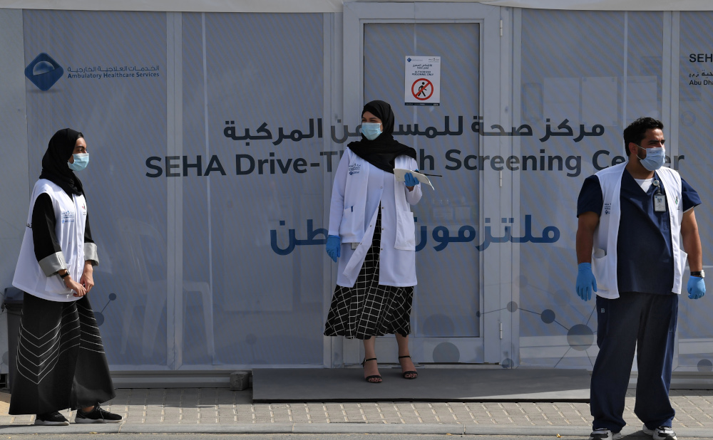 Medical volunteers wait outside a drive-through Covid-19 coronavirus testing centre in al-Khawaneej district of the gulf emirate of Dubai April 9, 2020. — AFP pic