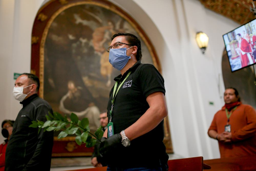Camera assistants from a television channel wearing face masks attend a mass that is recorded and televised, inside the Primary Cathedral chapel, amid the Covid-19 outbreak in Bogota April 5, 2020. ― Reuters pic
