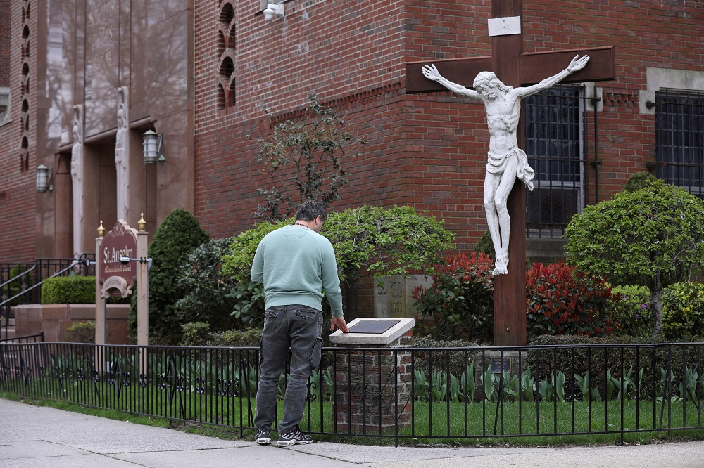 A man prays outside the closed Saint Anselm Church during the outbreak of coronavirus disease in the Brooklyn borough of New York April 10, 2020. ― Reuters pic