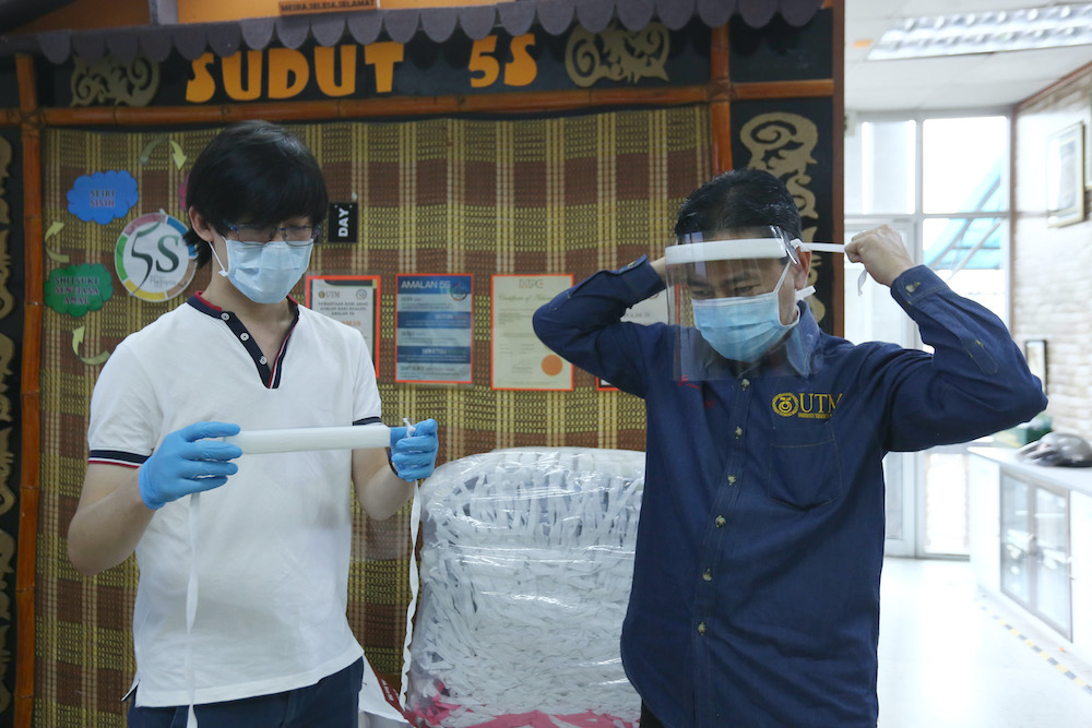 Johari (right) trying out the face shields made by Wong (left). — Picture courtesy of Hidayati Mokhtar.