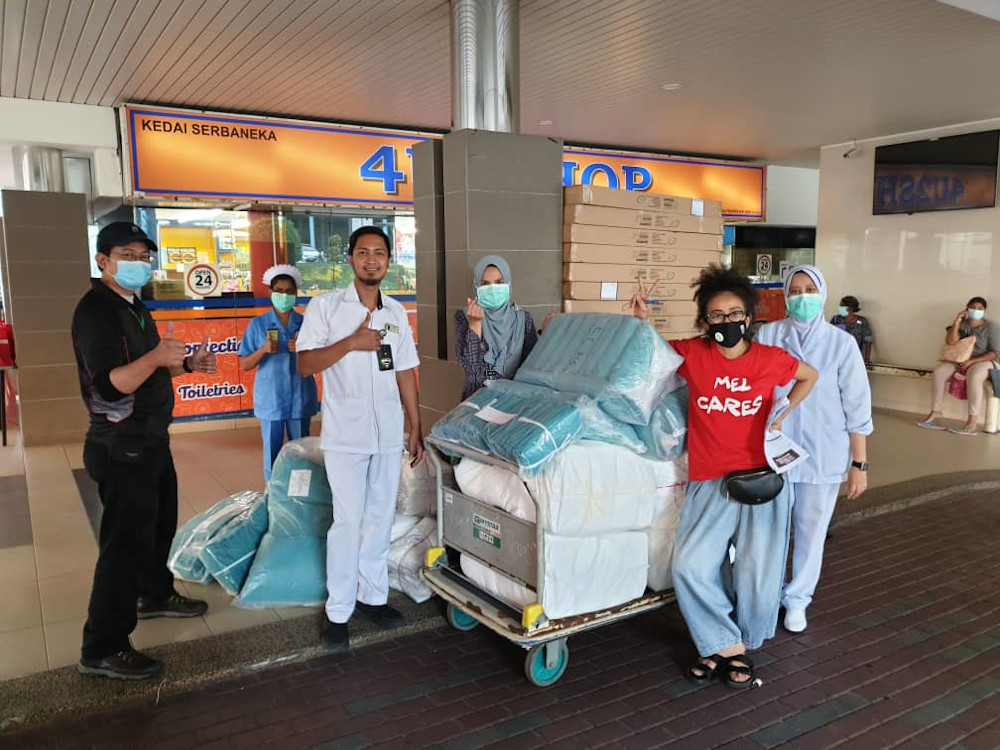 Fashion designer Melinda Looi (in red) handing the PPE gowns to Kuala Lumpur Hospital. — Picture by Melinda Looi
