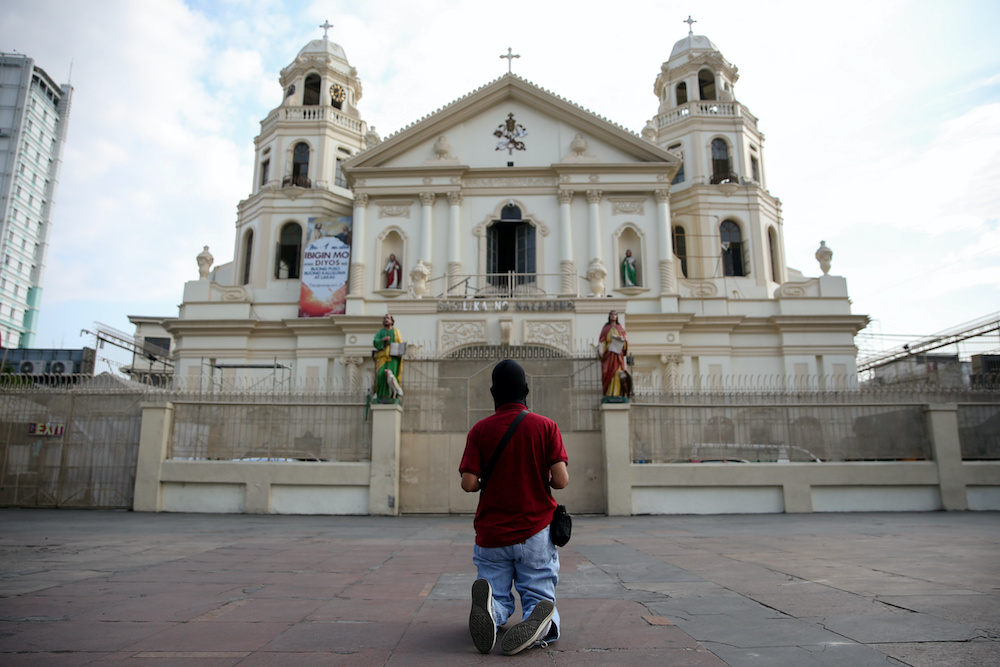A Filipino Catholic prays outside a closed church on Maundy Thursday amid the enforcement of home quarantine to contain the coronavirus disease (Covid-19), in Manila April 9, 2020. — Reuters pic