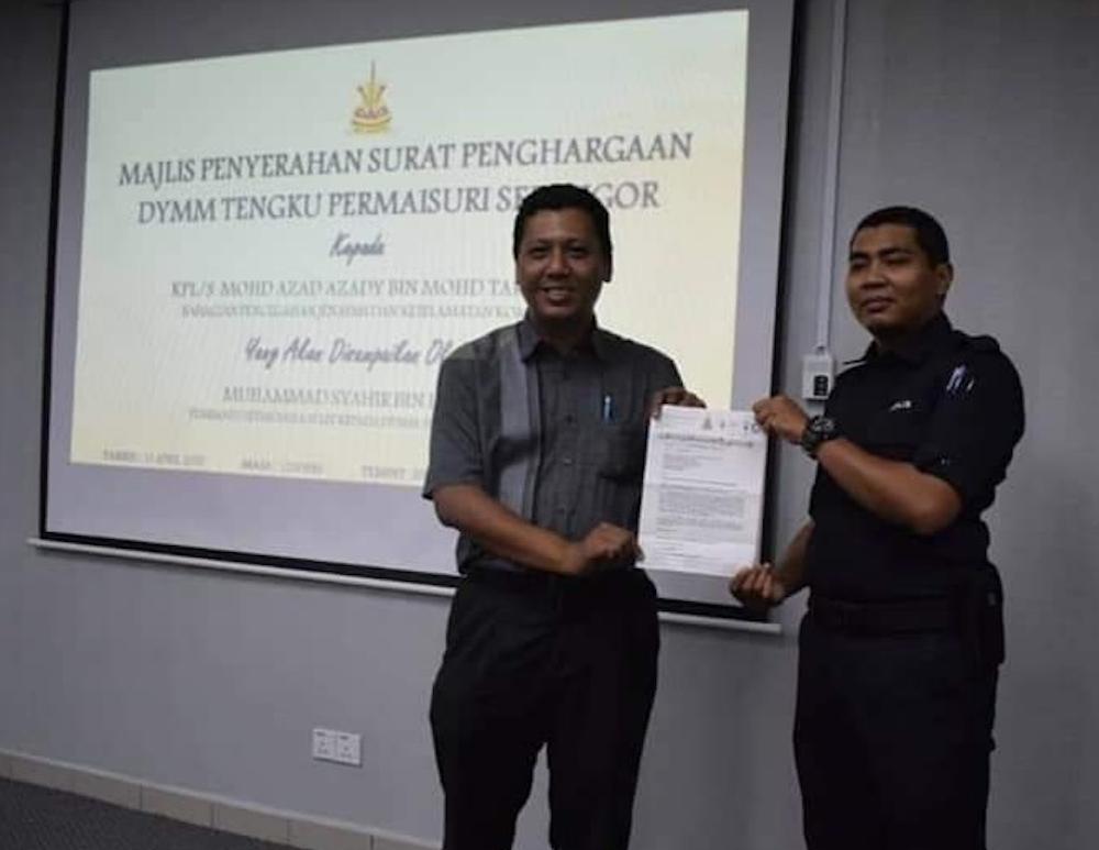 Shah Alam policeman Kpl/s Mohd Azad Azady Mohd Tarmizee (right) receiving the letter of commendation from Tengku Permaisuri Selangor Tengku Permaisuri Norashikin. The letter was presented by Muhammad Syahir Hasan, who is Sultan Selangor Sultan Sharafuddin
