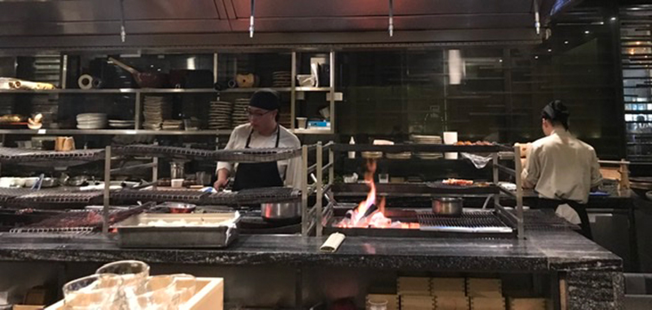 Open kitchen where chefs cook over charcoal grills or 'robata' style.