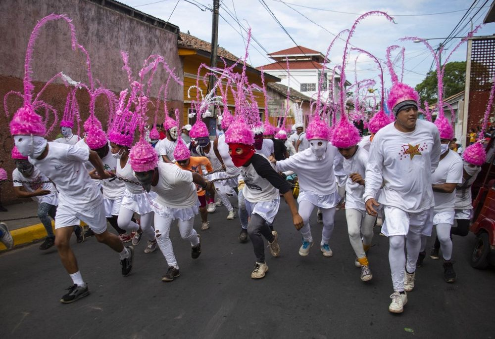 A group of men play 'Jews of Masatepe' during the procession 'The Chained' in which residents chase and capture people dressed as Judas to chain and drag them along the streets as punishment for betraying Jesus Christ, as part of the activities of Holy Week, in Masatepe, Nicaragua, April 10, 2020. — AFP pic