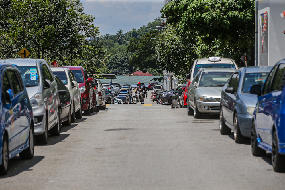 Cars parked on the streets in the morning on an otherwise empty street as residents at PPR Kerinchi head to work. — Picture by Hari Anggara