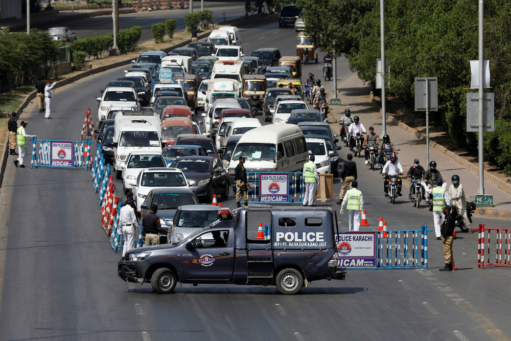 Police officers check drivers' documents to verify the purpose of movement at a blocked road, during a lockdown following the spread of the coronavirus disease (Covid-19), in Karachi, Pakistan April 9, 2020. — Reuters pic
