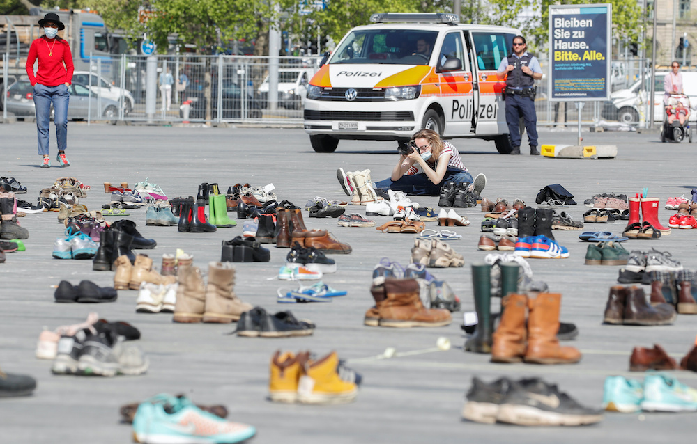 A person takes pictures of shoes placed, in place of live participants, by environmental activists of Swiss Klimastreik Schweiz movement to demonstrate against climate change, in Zurich, Switzerland April 24, 2020. — Reuters pic