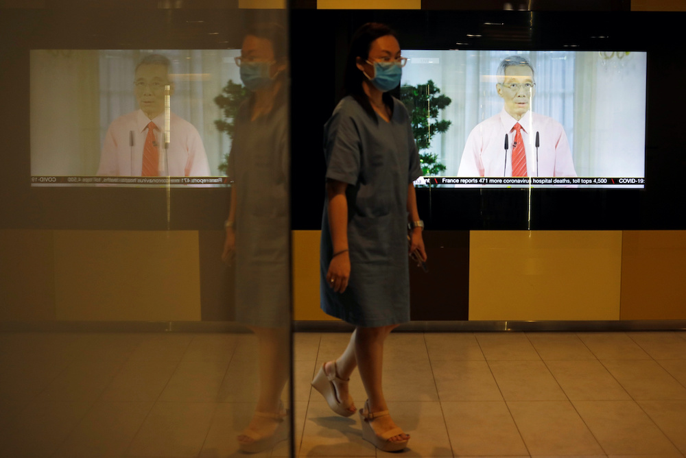 A woman with a face mask walks past a screen showing a telecast of Singapore's Prime Minister Lee Hsien Loong addressing the outbreak of coronavirus disease (Covid-19), at the central business district in Singapore, April 3, 2020. — Reuters pic