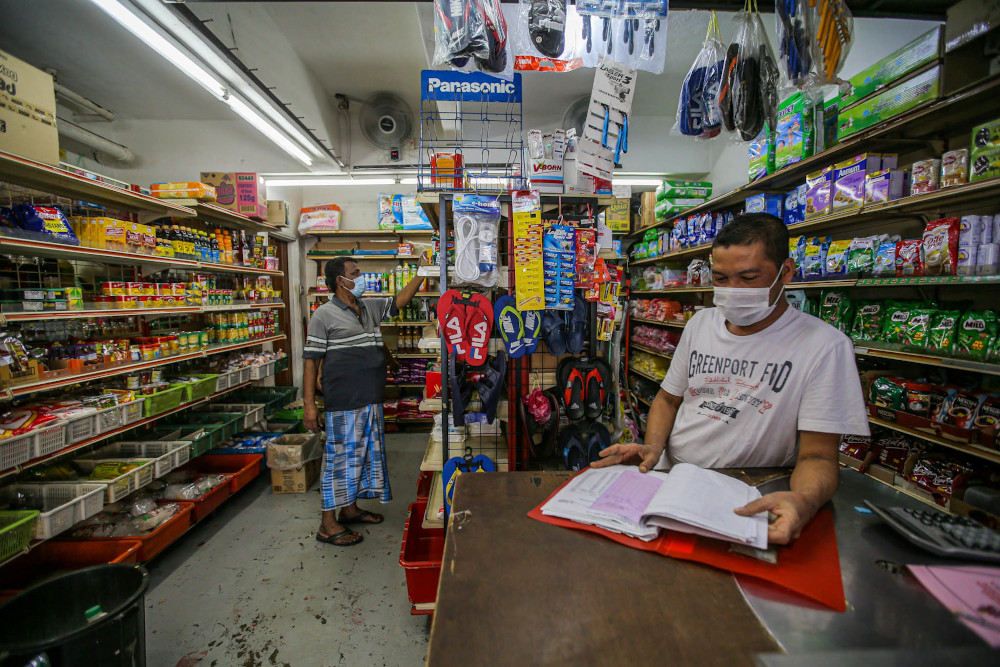 A shop supervisor checks his shop's supplies at the Taman Wilayah flats near the red zone area of Pasar Borong Kuala Lumpur. — Picture by Hari Anggara