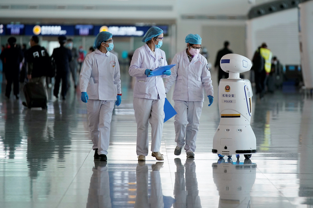 Medical workers walk by a police robot at the Wuhan Tianhe International Airport after travel restrictions to leave Wuhan, the capital of Hubei province and China's epicentre of the novel coronavirus disease (Covid-19) outbreak, were lifted, April 8, 20