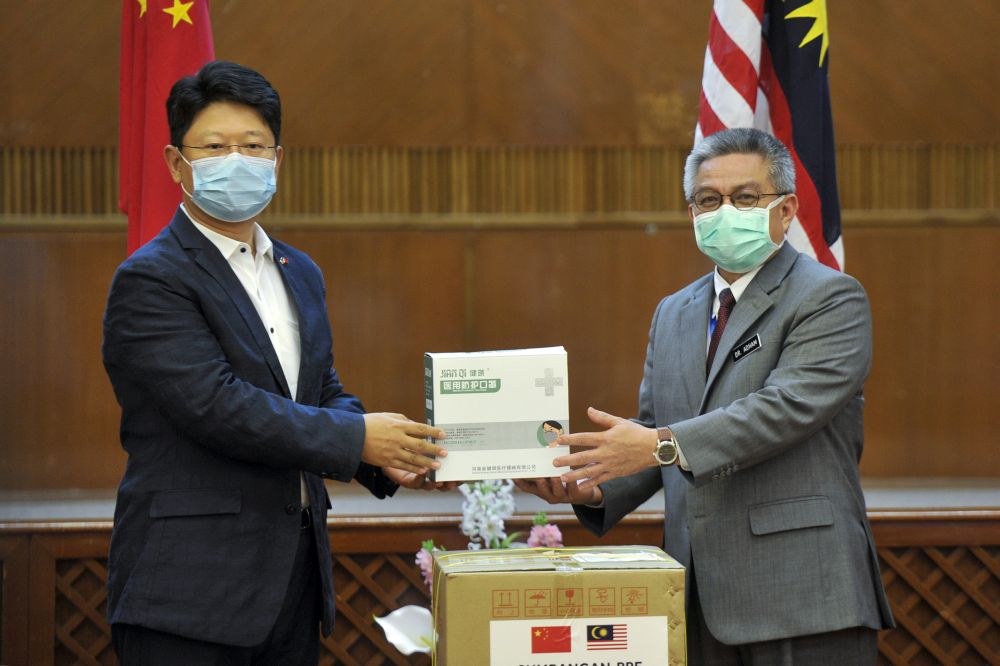 Datuk Seri Dr Adham Baba (right) receives a donation of face masks from Ambassador of China to Malaysia Bai Tian at the Health Ministry in Putrajaya April 2, 2020. — Picture by Shafwan Zaidon