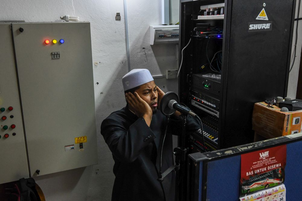 Mosque bilal Sharifuddin Sulaiman broadcasts a call of 'azan' at the At-Taqwa Mosque in Petaling Jaya April 21, 2020. — Picture by Shafwan Zaidon
