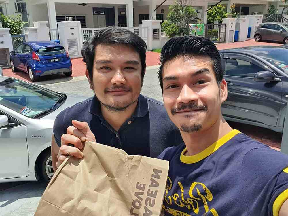 Benyamin (left) says he enjoys delivering food to customers and is keen to continue. — Picture courtesy of AirAsia