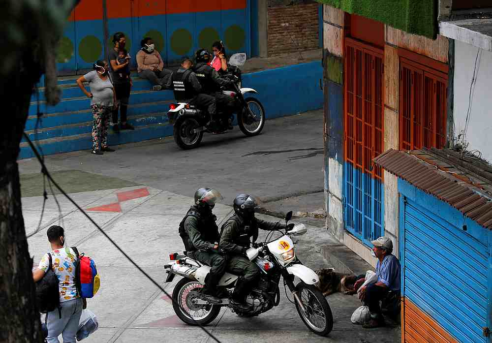Members of the Bolivarian national guard on motorcycles ask street vendors to go back home during a nationwide quarantine in Caracas, Venezuela April 20, 2020. — Reuters pic